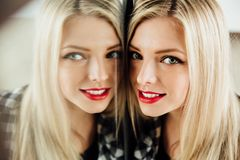 Portrait of beautiful young woman blonde girl and her reflection in mirror. stock photography