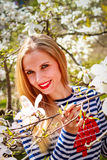 Portrait of beautiful young woman in blooming park on a sunny day. Smiling girl with Magnolia flowers Royalty Free Stock Photos