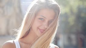 Portrait of beautiful young woman with with blue eyes and attractive smile. She stands in the middle of the street of a stock video footage