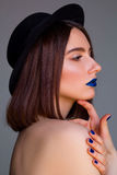 Portrait of beautiful young woman with blue lips and in hat. Bea Stock Photos