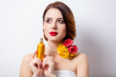 Portrait of beautiful young woman with bottle of perfume on the Royalty Free Stock Photo
