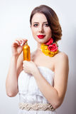 Portrait of beautiful young woman with bottle of perfume on the Stock Photo