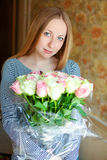 Portrait of a beautiful young woman with a bouquet of red roses Royalty Free Stock Photos