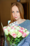 Portrait of a beautiful young woman with a bouquet of red roses Royalty Free Stock Photography