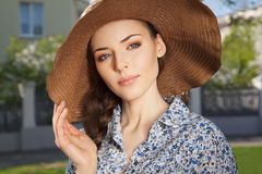 Girl with braid keeping hat with hand. Portrait of a beautiful young woman with braid hairdo keeping het hat with a hand, outdoors Stock Photo