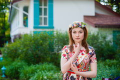 Portrait of a beautiful young woman in a bright dress on a head a wreath of flowers, lifestyle, youth Royalty Free Stock Photo