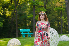 Portrait of a beautiful young woman in a bright dress on a head a wreath of flowers, lifestyle, youth Royalty Free Stock Image