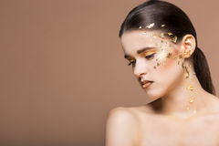Portrait of a beautiful young woman with bright golden make up Stock Photography