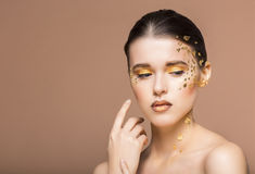 Portrait of a beautiful young woman with bright golden make up Stock Image