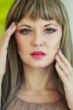 Portrait of a beautiful young woman. With bright make-up wearing a wig with long hair Stock Photography