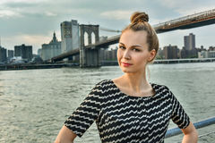 Portrait of the beautiful young woman with Brooklyn Bridge on the background. Stock Photos