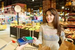 Woman Paying via Smartphone in Grocery Store Stock Image