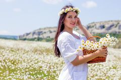 Portrait of a beautiful young woman in chamomile field. Happy girl collecting daisies. A girl resting in a field of chamomile. S royalty free stock images