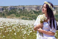 Portrait of a beautiful young woman in chamomile field. Happy girl collecting daisies. A girl resting in a field of chamomile. S Stock Photo
