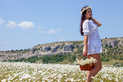 Portrait of a beautiful young woman in chamomile field. Happy girl collecting daisies. A girl resting in a field of chamomile. S Stock Photography