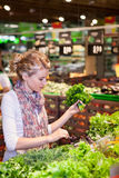 Portrait of beautiful young woman choosing green leafy vegetable Royalty Free Stock Photography