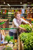 Portrait of beautiful young woman choosing green leafy vegetable Royalty Free Stock Image