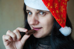 Portrait of a beautiful young woman in a christmas cap. With candy Royalty Free Stock Image