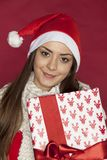 Portrait of beautiful young woman with a Christmas gift. On the red background Royalty Free Stock Image