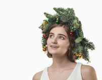 Portrait of beautiful young woman with Christmas wreath. Beautif. Portrait of beautiful young woman with Christmas wreath on a white baskground Royalty Free Stock Images