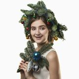Portrait of beautiful young woman with Christmas wreath. Beautif. Portrait of beautiful young woman with Christmas wreath on a white baskground Royalty Free Stock Photo