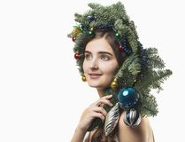 Portrait of beautiful young woman with Christmas wreath. Beautif. Portrait of beautiful young woman with Christmas wreath on a white baskground Stock Image