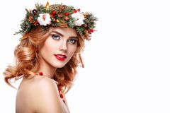 Portrait of beautiful young woman with Christmas wreath. Beautiful New Year and Christmas tree holiday hairstyle and makeup. Beauty girl portrait isolated on Royalty Free Stock Photo