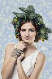 Portrait of beautiful young woman with Christmas wreath. Beautif. Portrait of beautiful young woman with Christmas wreath on a confetti blue baskground Royalty Free Stock Photos