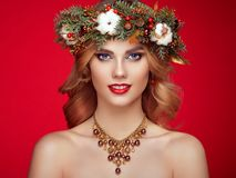 Portrait of beautiful young woman with Christmas wreath. Beautiful New Year and Christmas tree holiday hairstyle and makeup. Beauty girl portrait isolated on Stock Photography