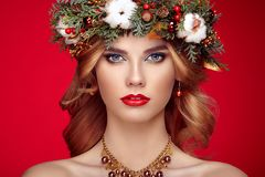 Portrait of beautiful young woman with Christmas wreath. Beautiful New Year and Christmas tree holiday hairstyle and makeup. Beauty girl portrait isolated on Royalty Free Stock Image