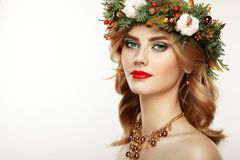Portrait of beautiful young woman with Christmas wreath. Beautiful New Year and Christmas tree holiday hairstyle and makeup. Beauty girl portrait isolated on Royalty Free Stock Images