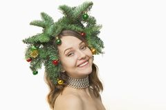 Portrait of beautiful young woman with Christmas wreath on a whi Royalty Free Stock Photography