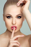 Portrait of beautiful young woman with clean skin, full lips, fresh face. Studio portrait. Woman holding finger near Stock Photo
