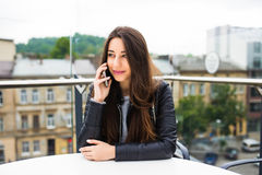 Portrait of beautiful young woman in coffee shop terrace, relaxing using smart phone, phone call conversation outdoors. Fashion fe. Portrait of beautiful young stock photos