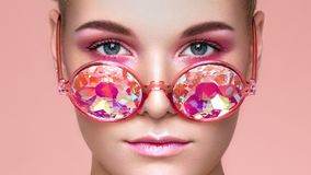 Portrait of beautiful young woman with colored glasses stock photo