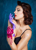 Portrait of a beautiful young woman with colored splashes hands Stock Photos