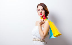 Portrait of beautiful young woman with colorful shopping bags on Stock Photography