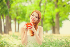 Portrait of beautiful young woman with cup of coffee on the wond. Erful park background Royalty Free Stock Photo