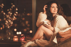 Portrait of beautiful young woman with cup of hot drink in cozy home interior royalty free stock photo