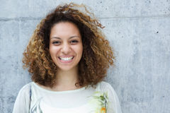 Portrait of a beautiful young woman with curly hair smiling outdoors. Close up portrait of a beautiful young woman with curly hair smiling outdoors Stock Image