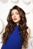 Portrait of beautiful young woman with curly long brown hair in blue dress Royalty Free Stock Photos
