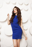 Portrait of beautiful young woman with curly long brown hair in blue dress Stock Image