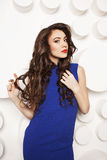 Portrait of beautiful young woman with curly long brown hair in blue dress Royalty Free Stock Photo