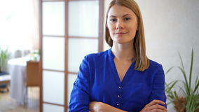 Portrait of beautiful young woman in dark blue blouse standing in living room smiling arms crossed. Portrait of beautiful attractive young woman in dark blue stock video