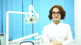 Portrait of beautiful young woman dentist standing arms crossed in the dental clinic cabinet. Confident doctor in stock video footage