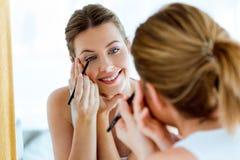 Beautiful young woman doing make-up near mirror at home. Portrait of beautiful young woman doing make-up near mirror at home Stock Image
