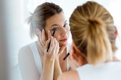 Beautiful young woman doing make-up near mirror at home. Portrait of beautiful young woman doing make-up near mirror at home Stock Photos
