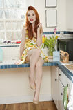 Portrait of a beautiful young woman in a dress at kitchen counter Stock Image