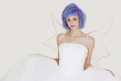 Portrait of beautiful young woman dressed as angel with dyed hair against gray background Royalty Free Stock Image