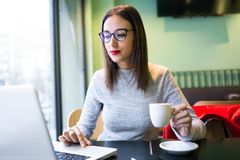 Beautiful young woman drinking coffee while using her laptop in the coffee shop. Stock Photography